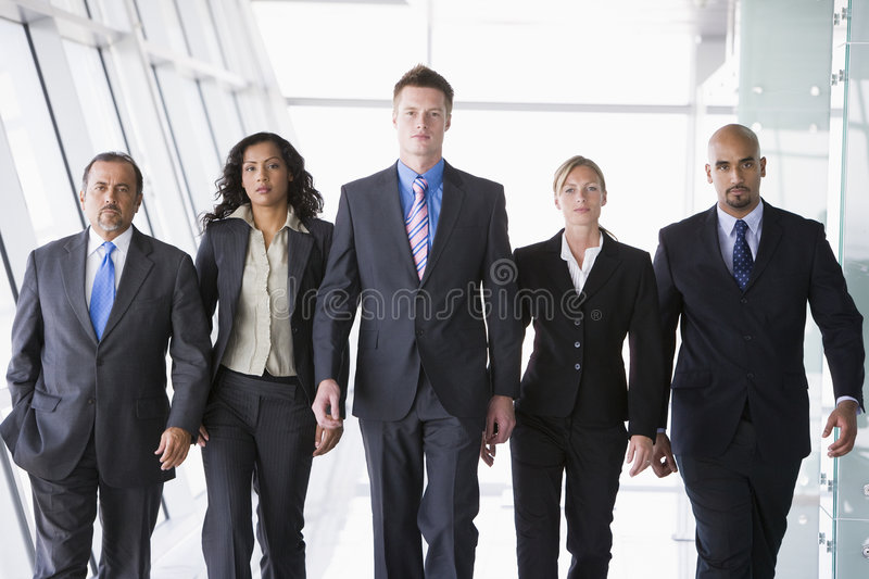 Group of business people walking towards camera stock photo