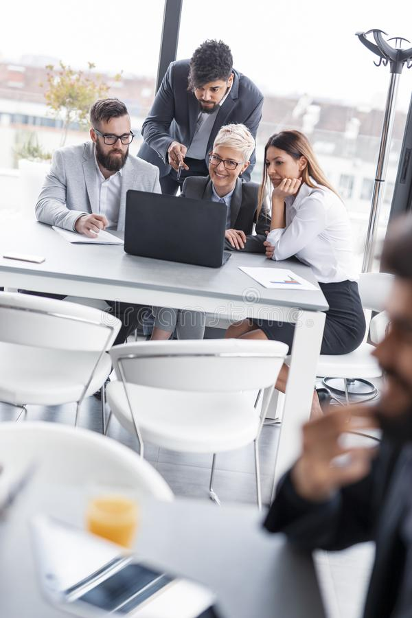 Busy day in an office. Group of business people working in an office, brainstorming and analysing data royalty free stock image