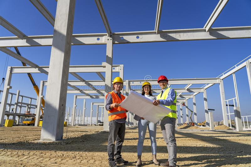 Group of Business People in Yellow and Red Hardhats Discuss a Project on Site Under Construction stock photo