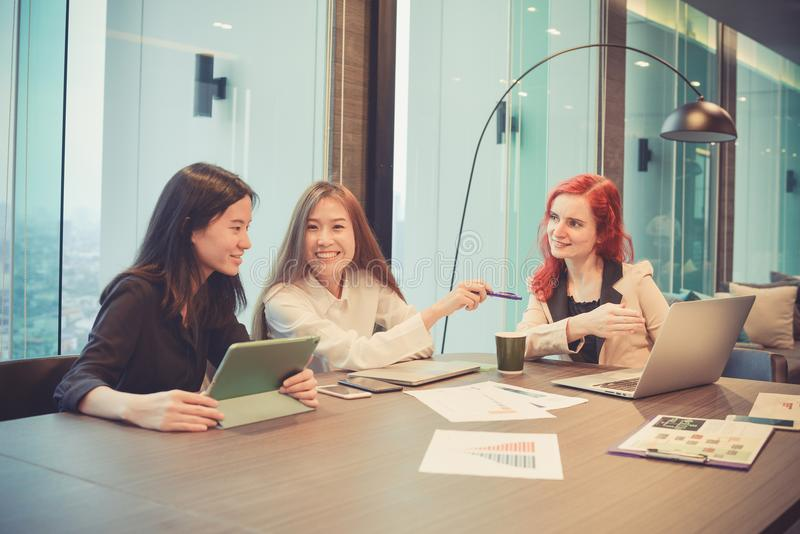 Group of business women meeting in a meeting room with blank screen, sharing their ideas, Multi ethnic.  royalty free stock photos