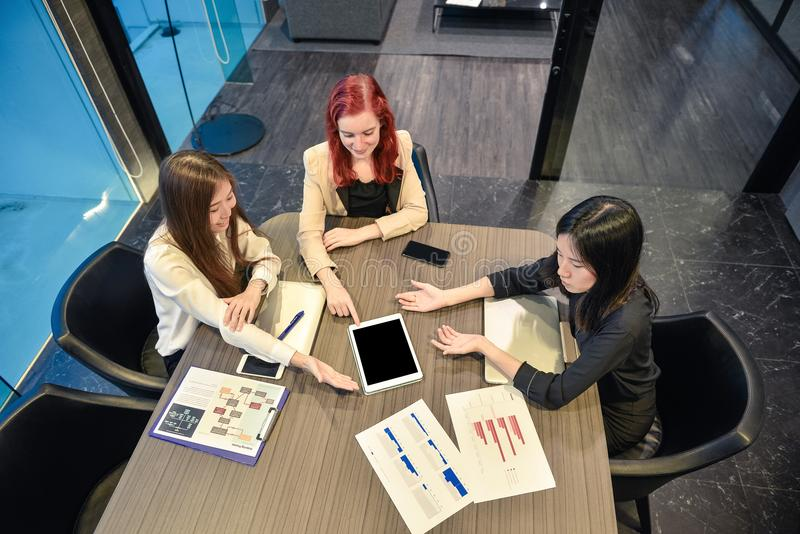 Group of business women meeting in a meeting room with blank screen, sharing their ideas, Multi ethnic.  royalty free stock images