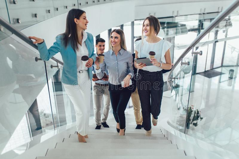Businessmen and businesswomen walking and taking stairs in an office building stock photography