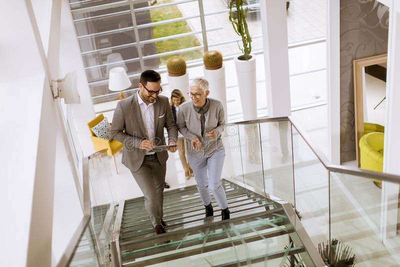 Businessmen and businesswomen walking and taking stairs in an of stock photography