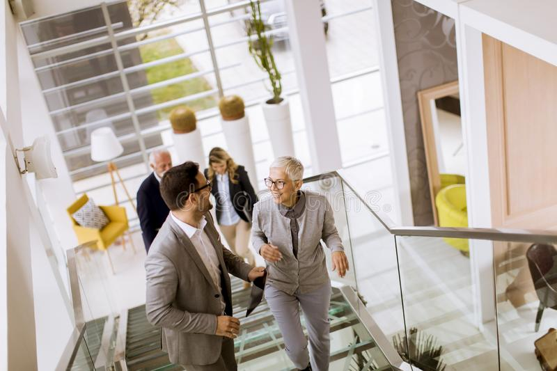 Businessmen and businesswomen walking and taking stairs in an of royalty free stock photo
