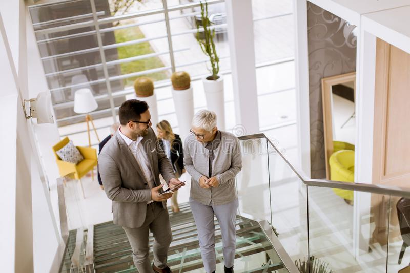 Businessmen and businesswomen walking and taking stairs in an of stock photos