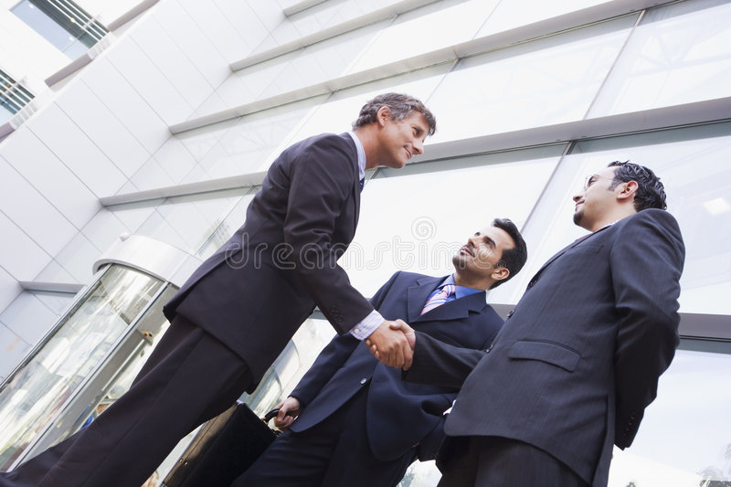 Group of businessmen shaking hands outside office royalty free stock photo