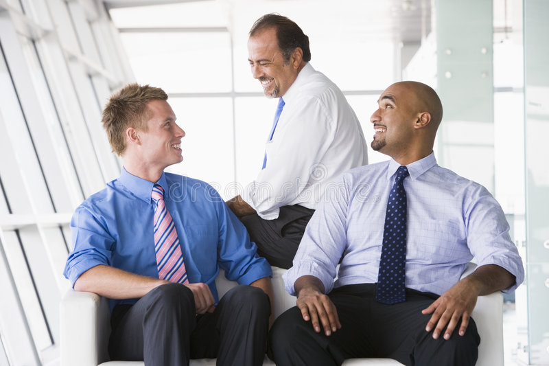 Group of businessmen talking in lobby stock images