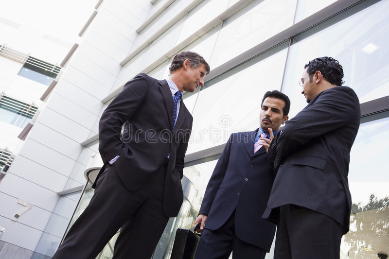 Group of businessmen talking outside office royalty free stock photo