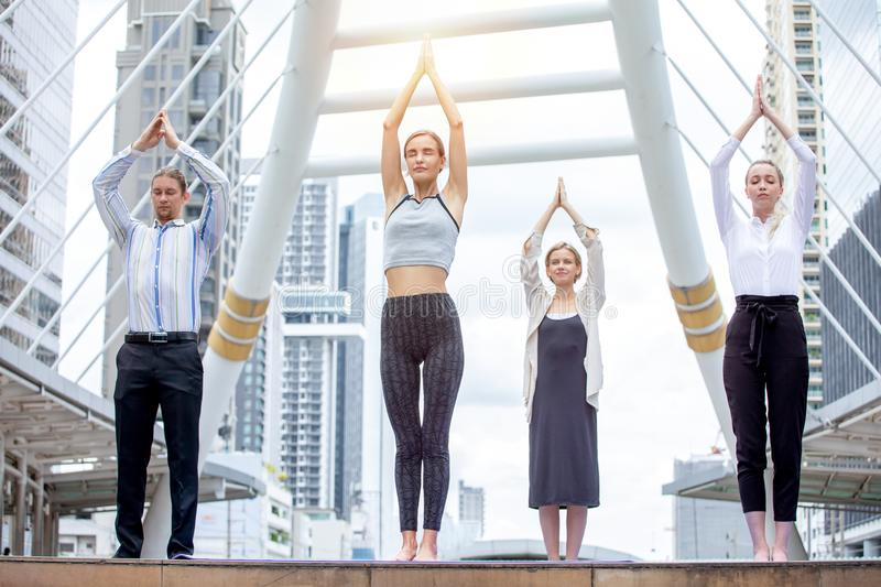 Group businesspeople doing yoga with trainer in urban city outdoor. Calm man and women relaxing meditating take break at workplace. Group businesspeople doing stock photography