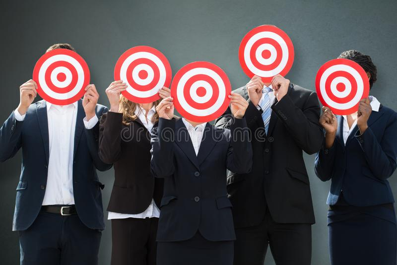 Group Of Businesspeople Hiding Their Faces Behind Dartboard royalty free stock photography