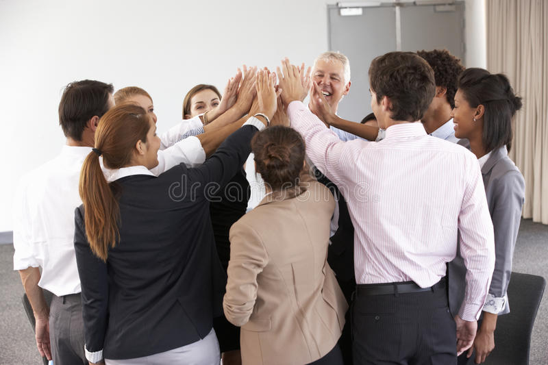 Group Of Businesspeople Joining Hands In Circle At Company Seminar royalty free stock photo