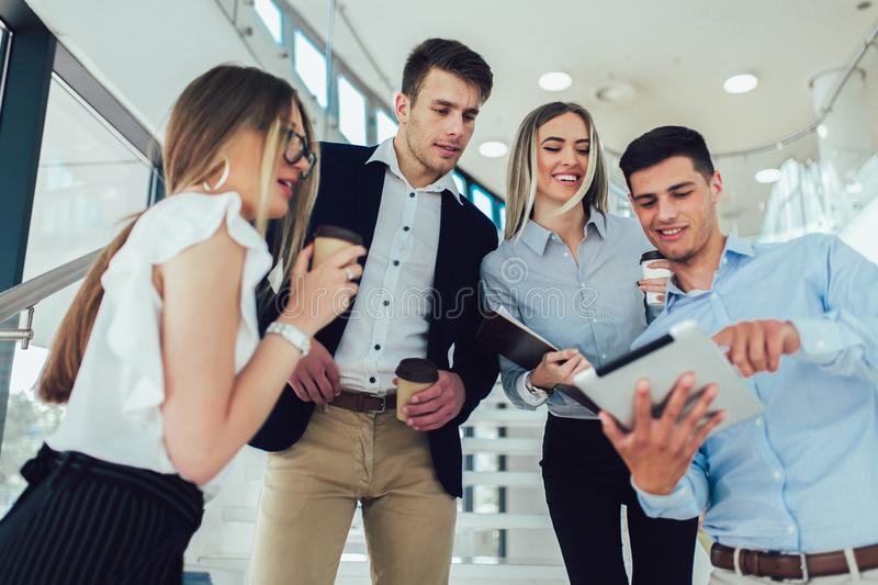 Businesspeople using a digital tablet together in office building. Group of businesspeople using a digital tablet together in office building royalty free stock image
