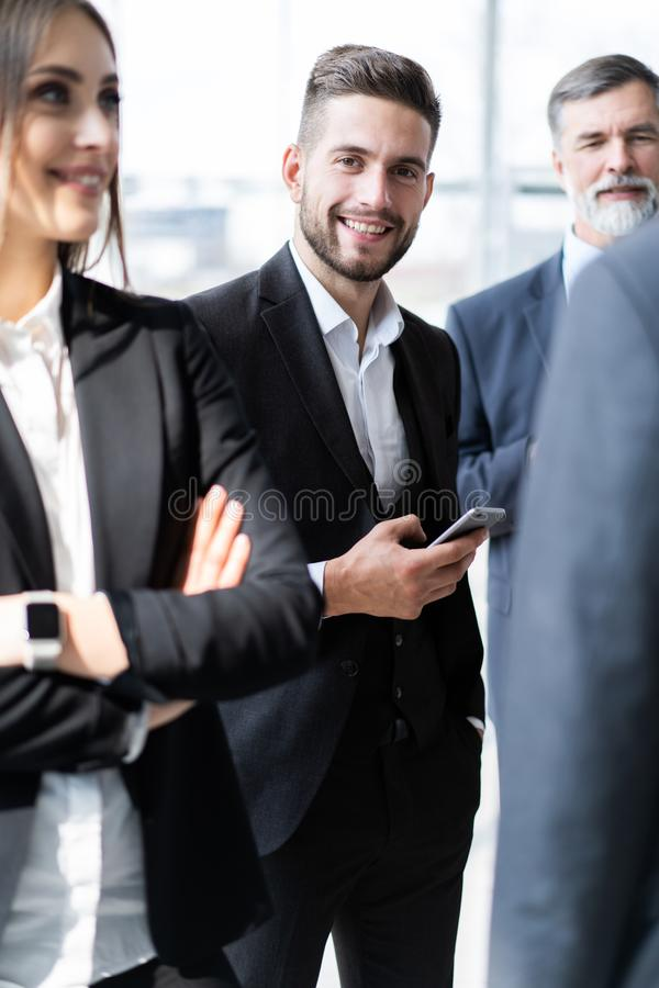 Group of Busy Business People Concept. Business team discussing work in office building hallway. stock image