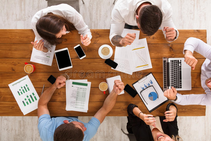 Group of busy business people working in office, top view. Of wooden table with mobile phones, laptop, tablet and documents papers with diagram. Men and women stock images