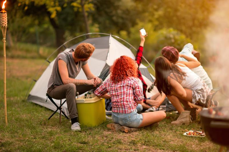 Group of campers photographing selfie in nature. Group of campers photographing selfie for memory of summer music festival on sunset in nature royalty free stock images