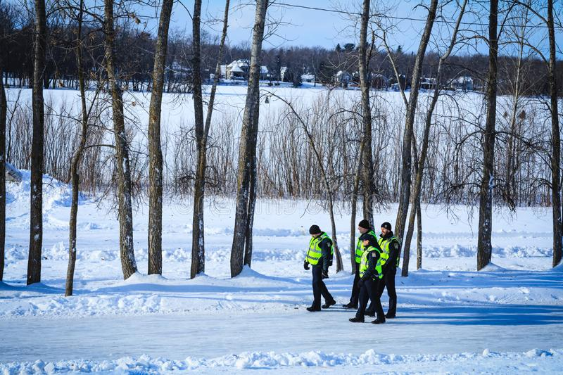 A group of Canadian policemen on patrol during the winter time. Police officers in investigation mission near a frozen river royalty free stock photography