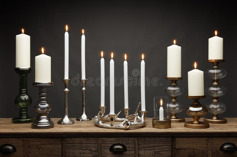 A group of candle sticks and glowing candles, shot on a wooden table, with a dark grey background stock photo