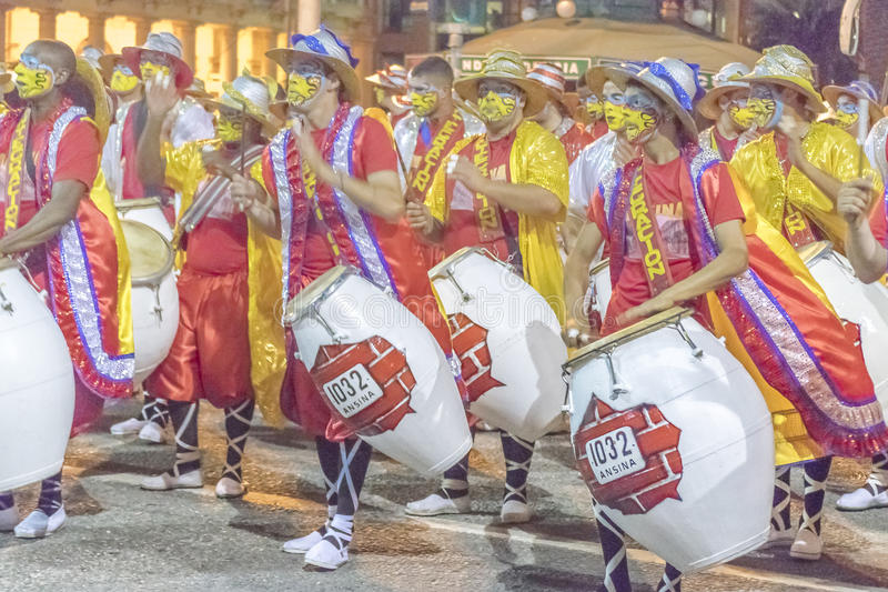 Group of Candombe Drummers at Carnival Parade of Uruguay. MONTEVIDEO, URUGUAY, JANUARY - 2016 - Costumed men drummers playing traditional music called candombe royalty free stock photography
