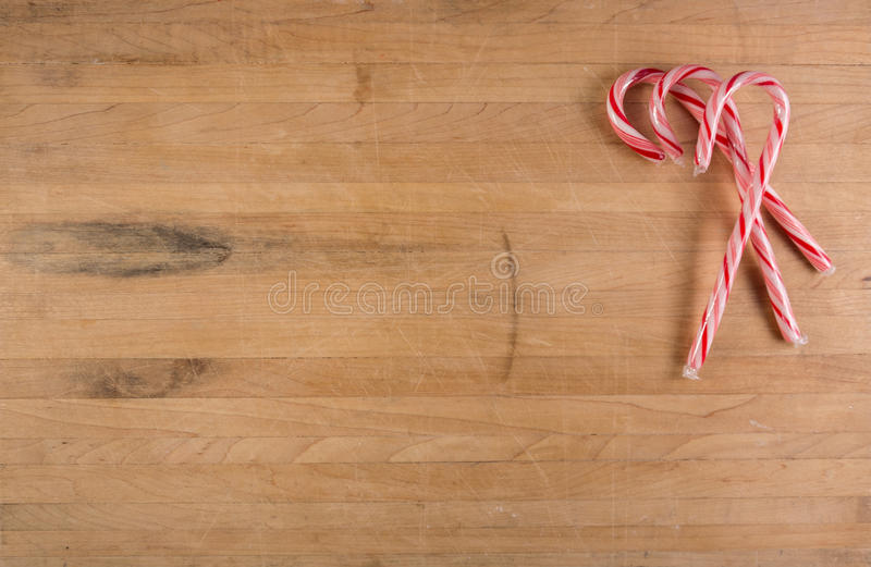 Group of Candy Canes Sits on Cutting Board. Three candy canes sits on a worn cutting board with room for text stock photo