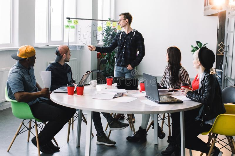 Group of casually dressed businesspeople discussing ideas in the office. Creative professionals gathered at the meeting royalty free stock photography