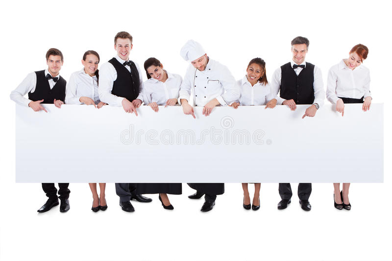 Group of catering staff holding a blank banner. Large group of catering staff holding a blank banner with copyspace for your text including a chef waiters