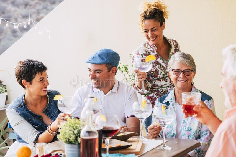 Group of caucasian cheerful happy people together drinking some wine having fun in friendship - different ages generation with stock photos