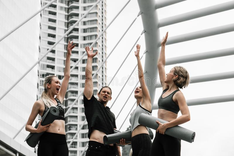 Group of caucasian yoga team cheering up team spirit by raise hands up together royalty free stock images