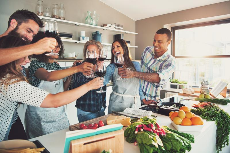 Group of celebrating friends at cooking party royalty free stock photography