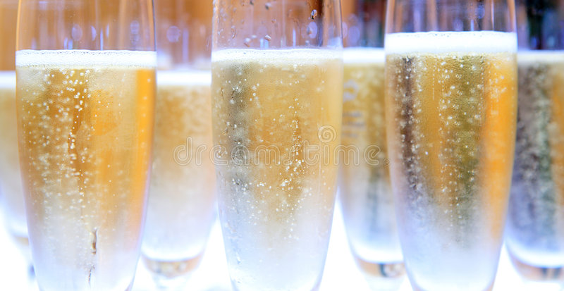Group of Champagne glasses filled with bubbles. At a wedding or birthday party stock photography