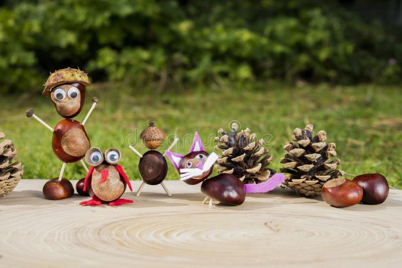 Group of character or figurines made with chestnuts on a wooden background in a sunny day stock photo