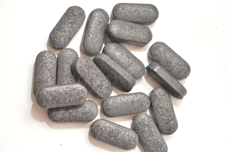 Group of charcoal pills on white background. Medicine wellness bpttle glass black pills medicine stock photo