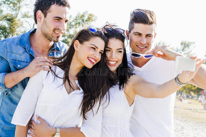 Group of cheerful and beautiful young people taking photos of th. Group of cheerful and beautiful young people taking selfies of themselves stock photos