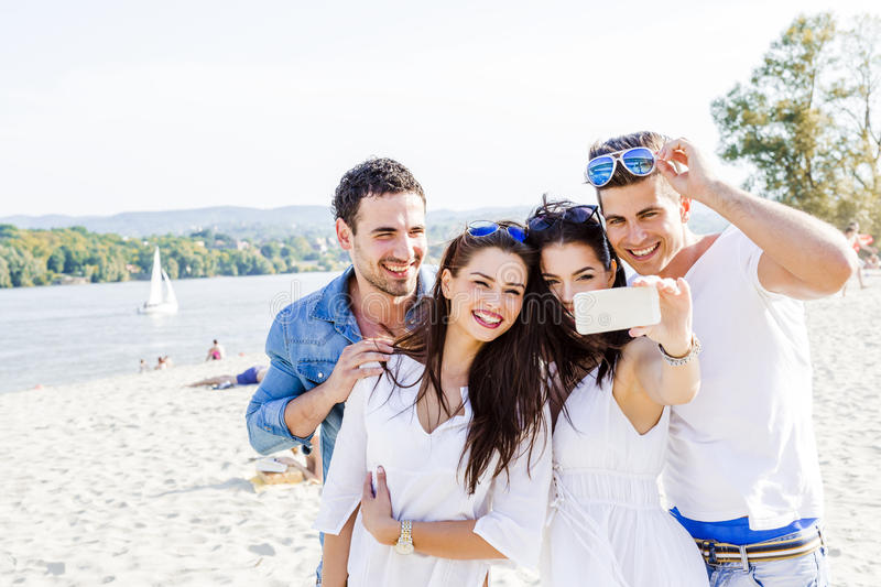 Group of cheerful and beautiful young people taking photos of th. Group of cheerful and beautiful young people taking selfies of themselves stock images
