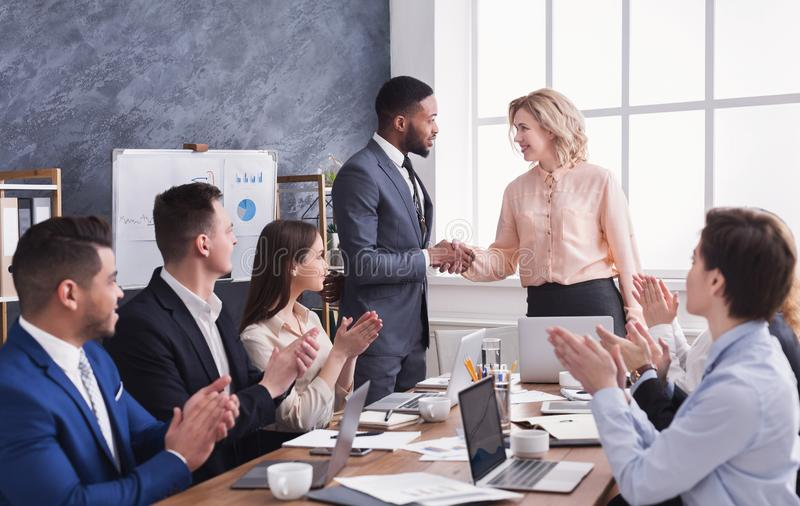 Group of cheerful business people sitting at meeting stock photo