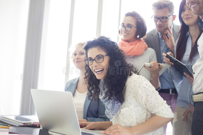 Group of cheerful businesspeople with laptop at desk in creative office royalty free stock images