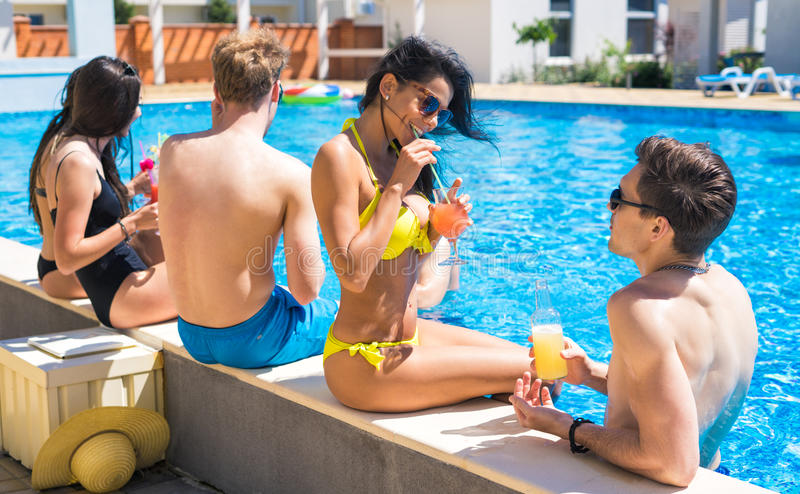Group of cheerful couples drinking cocktails in the pool. Party at smimming pool. Group of cheerful couples drinking cocktails and beer in the pool. They look royalty free stock images
