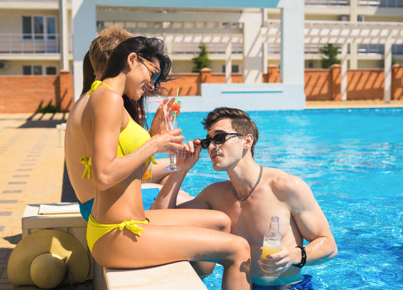 Group of cheerful couples drinking cocktails in the pool. Party at smimming pool. Group of cheerful couples drinking cocktails in the pool. Guy tries to meet a royalty free stock photo