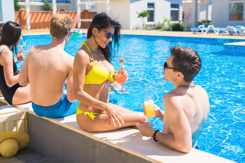 Group of cheerful couples drinking cocktails in the pool. Party at smimming pool. Group of cheerful couples drinking cocktails in the pool. They are talking to stock photo
