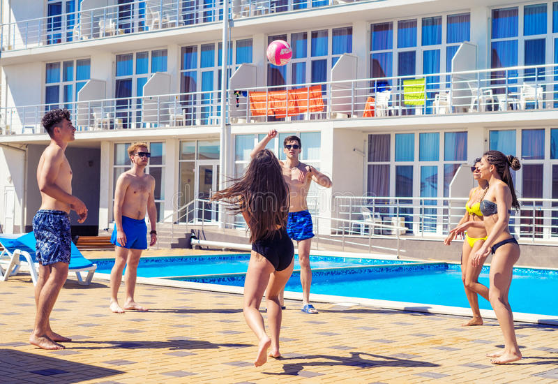 Group of cheerful couples friends playing volleyball. Party at smimming pool. Group of cheerful couples friends playing volleyball. Happy youth time stock image