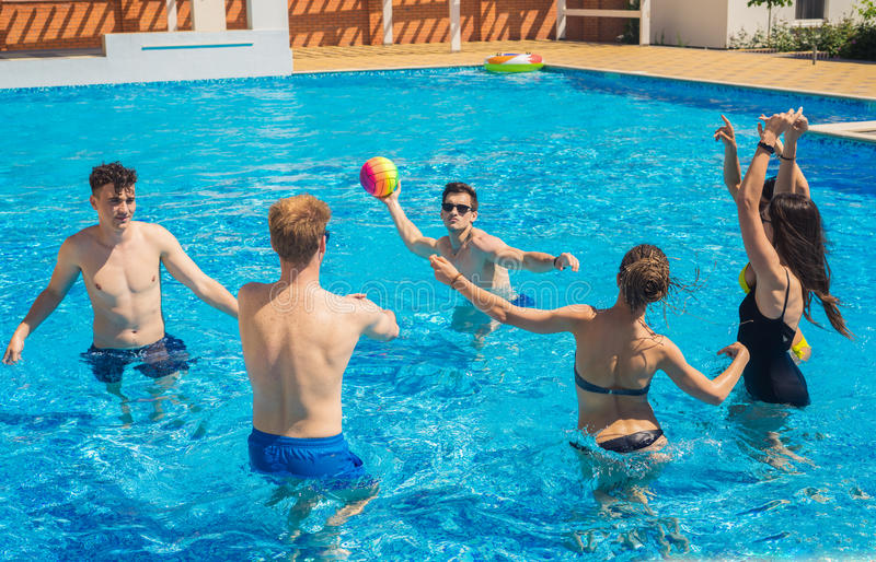 Group of cheerful couples friends playing water volleyball. Party at smimming pool. Group of cheerful couples friends playing water volleyball royalty free stock photos