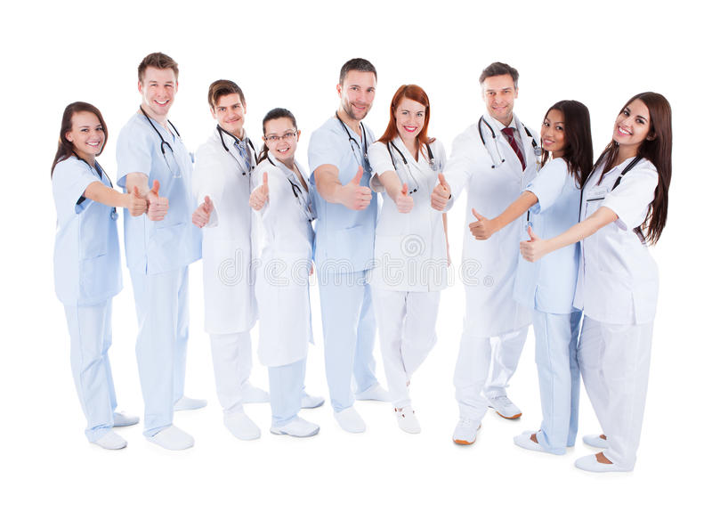 Group of cheerful doctors showing thumbs up stock photo