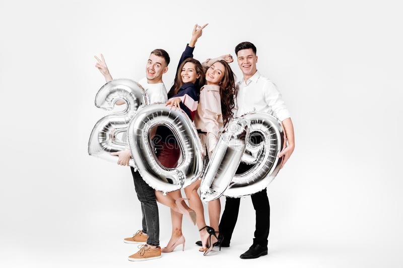 Group of cheerful friends of two girls and two guys dressed in stylish clothes are holding balloons in the shape of stock photography
