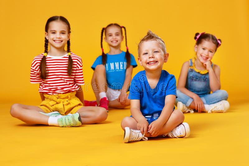 Group of cheerful happy children on colored yellow background stock image