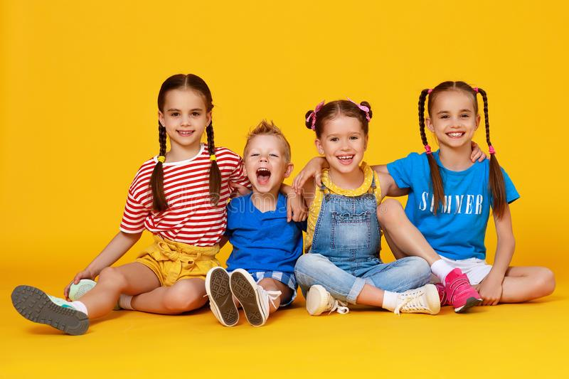 Group of cheerful happy children on colored yellow background stock photo