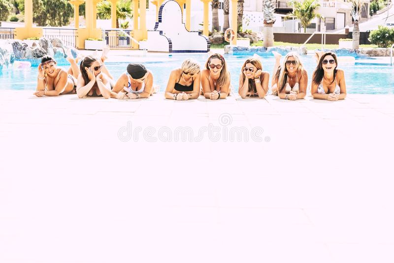 Group of cheerful happy people lay down at the pool on a white floor - friendship and young women on vacation concept - friends. Having fun together during royalty free stock images