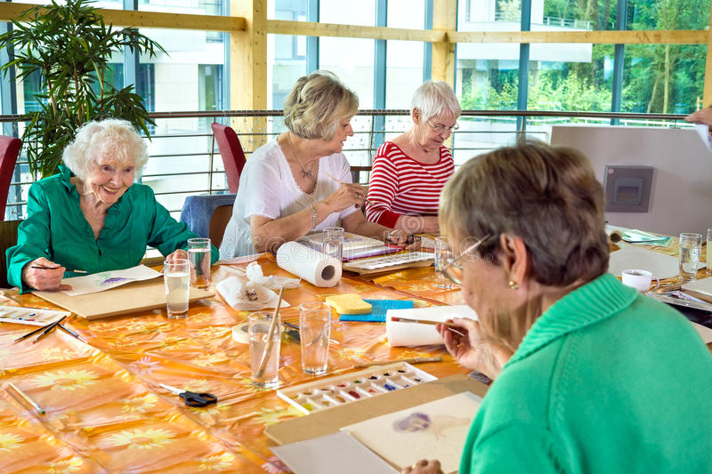 Group of cheerful older students painting together. Group of four female cheerful older students painting together at table in spacious room with large windows royalty free stock images