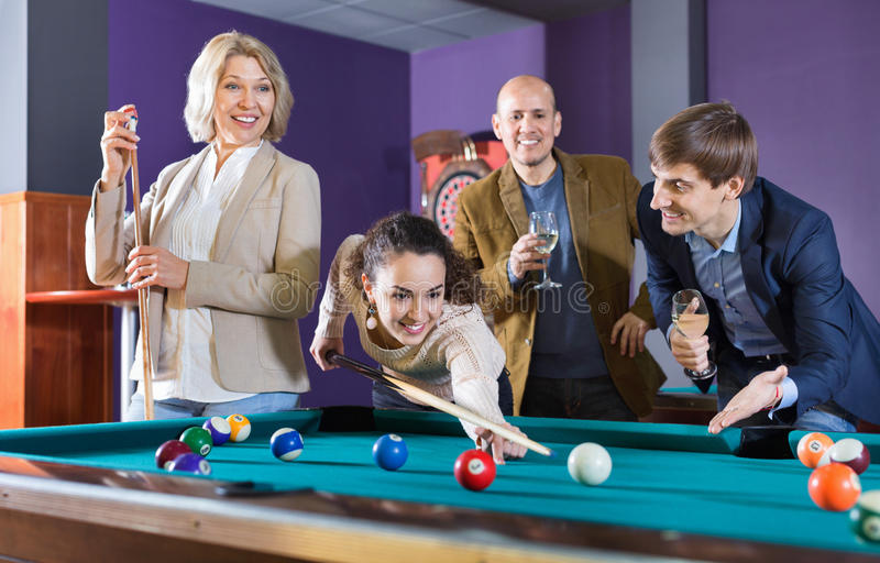 Group of cheerful pretty positive friends playing billiards stock photos