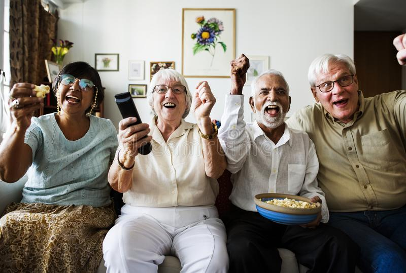 Group of cheerful senior friends sitting and watching TV together royalty free stock photo