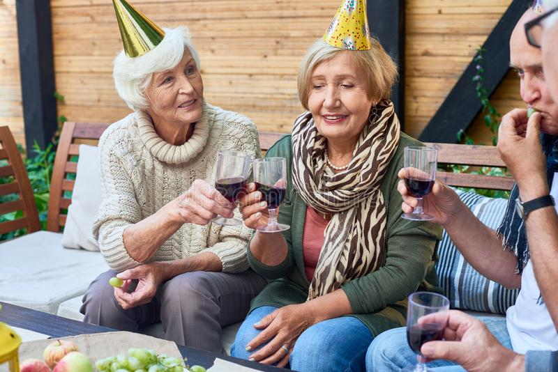 Happy Birthday Party. Group of cheerful senior people wearing holiday caps celebrating birthday on outdoor terrace with friends, clinking wine glasses and royalty free stock photography