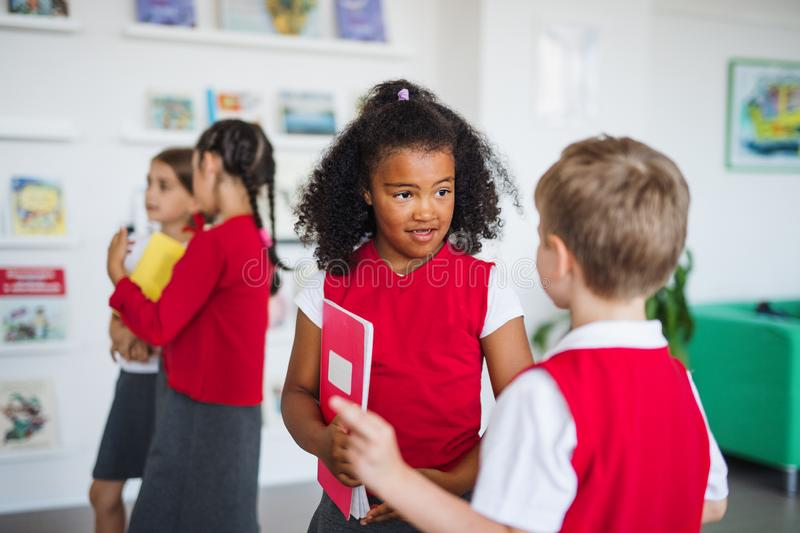 A group of cheerful small school kids in corridor, standing and talking. royalty free stock photos